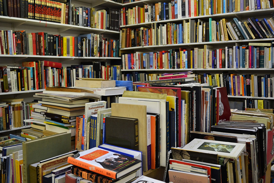 Books on table and shelves in a room.